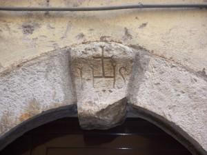 Chiave di volta di palazzo di corso Italia con Trigramma di Cristo e Chiodi della Crocifissione